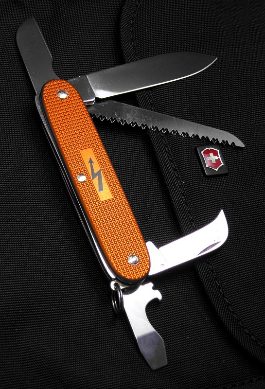 This is a new configuration in a Victorinox 93mm Alox frame.  This knife is part of a short special-run from July 2011 of only 50 pieces.  Each knife is numbered on the small Electrician's/Sheepsfoot blade. The bright Orange (Tangerine) anodized Alox scales are also not very common.  The special electrical symbol in the panel has been seen on only 1 earlier Electrician Solo special.  Apparently there was a mistake during manufacturing and the knives needed to be disassembled and reassembled, This left a few extra marks around the rivets on some knives.